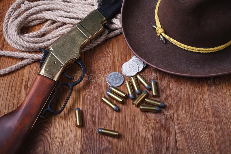 Wild west rifle, ammunition and silver dollars. On wooden table royalty free stock photography