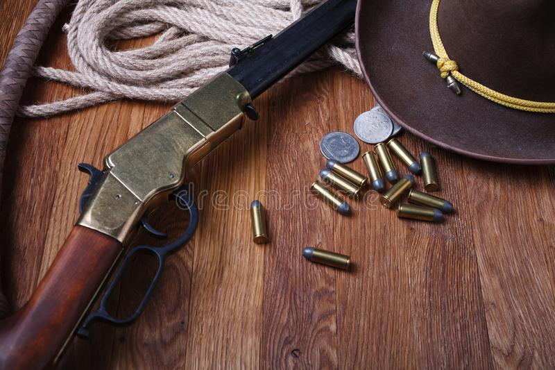 Wild west rifle, ammunition and silver dollars. On wooden table royalty free stock images