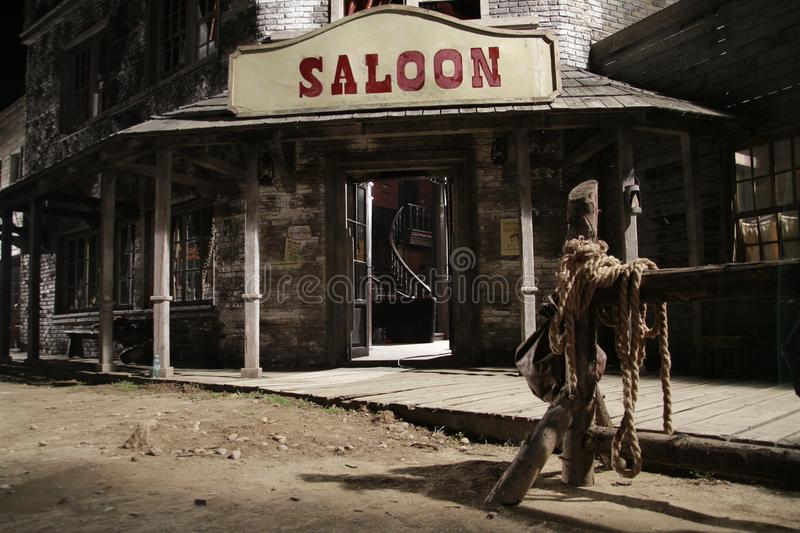 Wild west saloon front with hitch rack at night stock photo