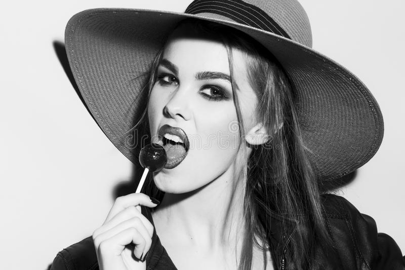 Wild young blonde woman black and white portrait with sugar candy. Wild young blonde woman black and white portrait with bright make up in hat and leather jacket stock photography
