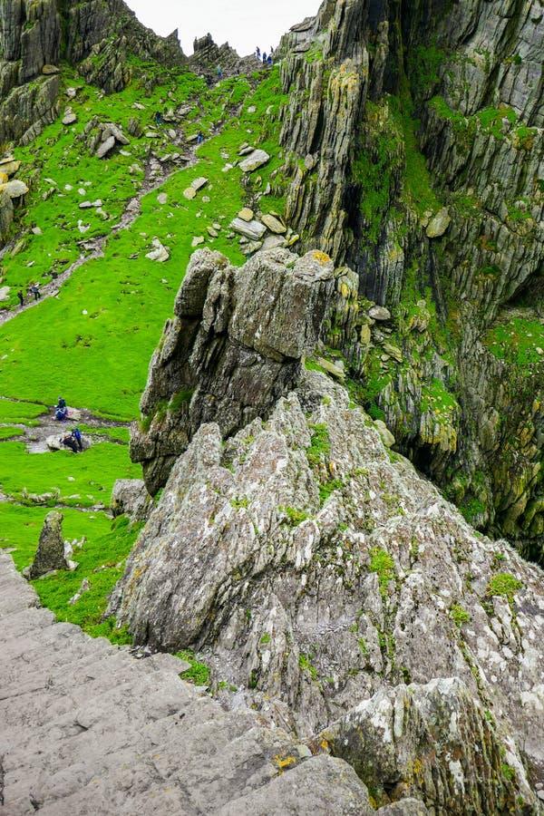Wilde atlantische Weise: Steile Tonschritte fahren zu Kloster Skellig Michael fort, da Wanderer stillstehen und erforschen unten  lizenzfreie stockfotografie