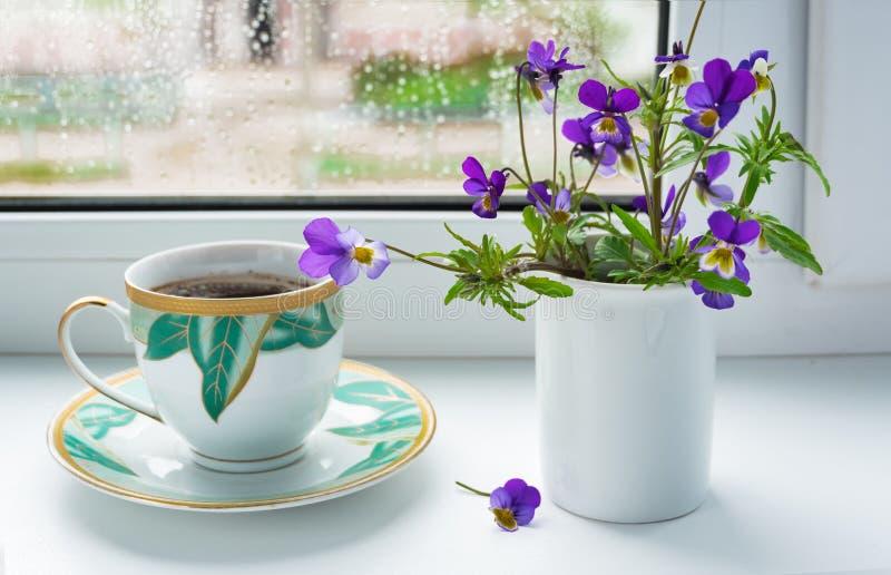 Wilde bloemen pansies en een Kop van koffie op de vensterbank in regenachtig weer royalty-vrije stock afbeelding