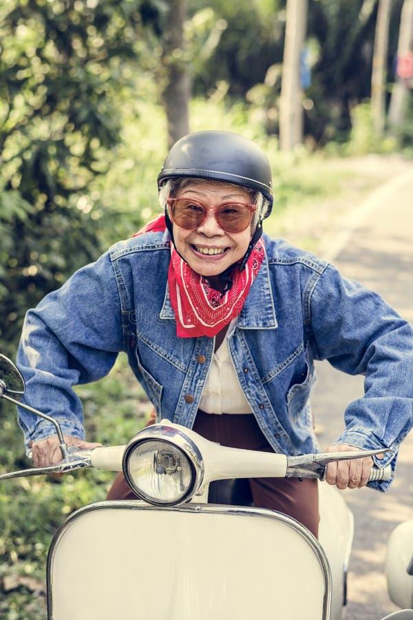 Wilde en vrije hogere vrouw die uitstekende motorfiets berijden royalty-vrije stock afbeeldingen