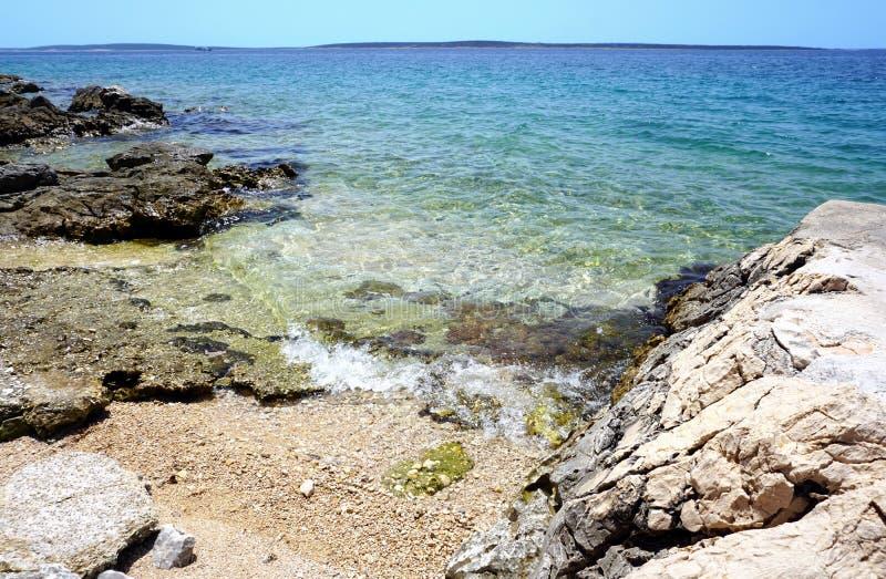 Wilde overzeese kust mooie blauwe lagune met kiezelsteenstrand royalty-vrije stock foto