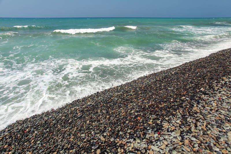 Wilder natürlicher Strand mit größtenteils den dunklen Kieselsteinen naß vom Meer, Himmel im Hintergrund stockbilder