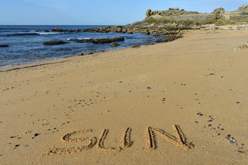 """Wilder Strand mit dem Wort """"sun† geschrieben in den Sand Felsen, goldener Sand, blaues Wasser, kleine Wellen Prähistorische  lizenzfreie stockbilder"""