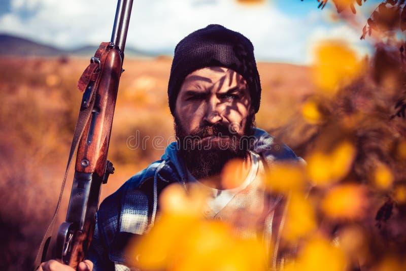 Wilderer mit dem Gewehr, das einige Rotwild beschmutzt Illegaler Jagdwilderer in der Forest Hunting-Jahreszeit Wildererkonzept stockfotos