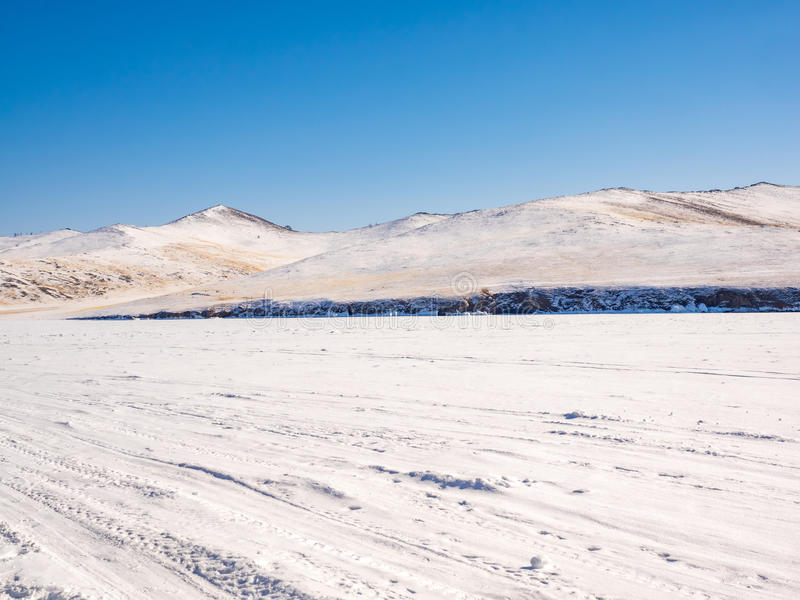 Wilderness of frozen water covered with snow in Lake Baikal. Near the snow mountain stock photo