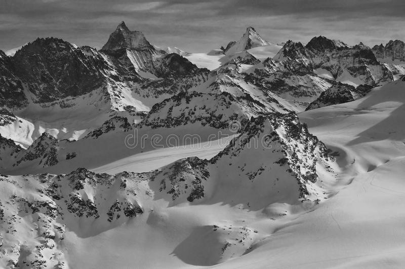 Wilderness skiing and the Matterhorn. Monochrome of ski tracks in a glacial wilderness with the matterhorn and Dent d'Herens on the skyline stock images