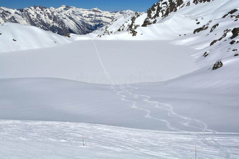 Wilderness skiing. Ski tracks cross a frozen lake in the mountains in Switzerland on a beautiful sunny day royalty free stock images