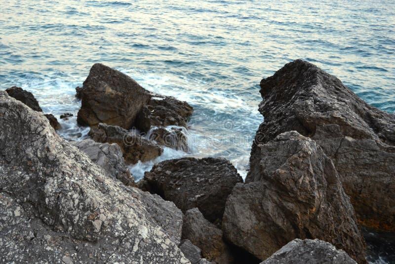 Wildes Seepanorama umgeben mit scharfen Felsensteinen im Sommer am sonnigen Sonnenuntergangtag Schönheit und Kraft des tiefen Was stockfotos
