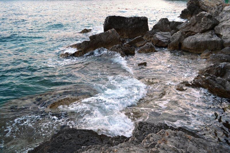 Wildes Seepanorama umgeben mit scharfen Felsensteinen im Sommer am sonnigen Sonnenuntergangtag Schönheit und Kraft des tiefen Was lizenzfreie stockfotografie