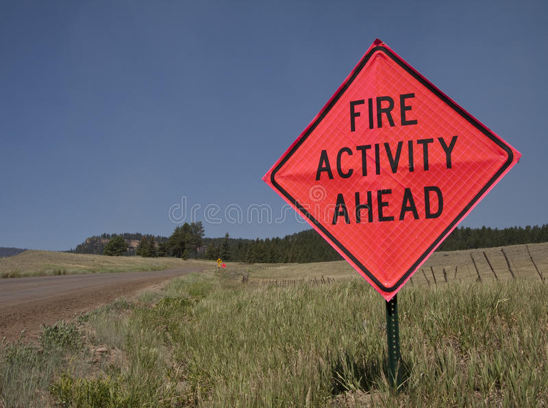 Wildfire road sign. A red road sign by a rural dirt road warns of a forest fire ahead stock photography