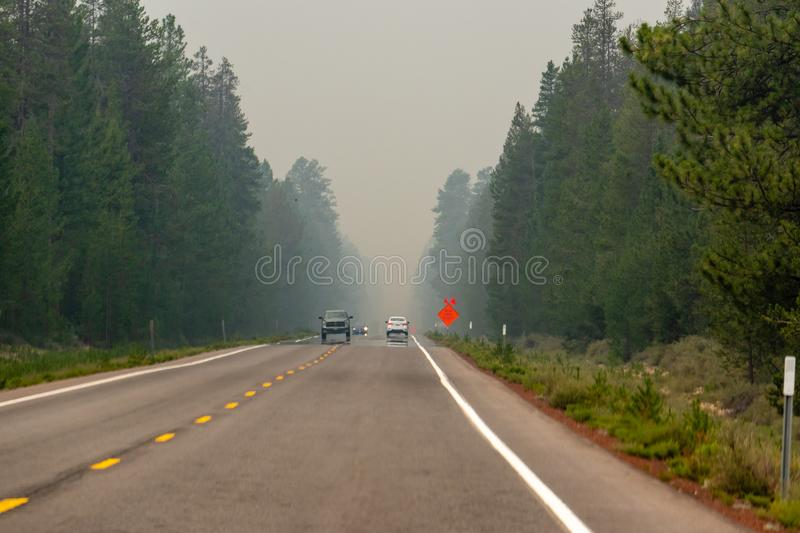 Smoke Filled Highway. Wildfire smoke filled highway in Southern Oregon, sign at roadside `SMOKE LIMITED VISIBILITY stock image
