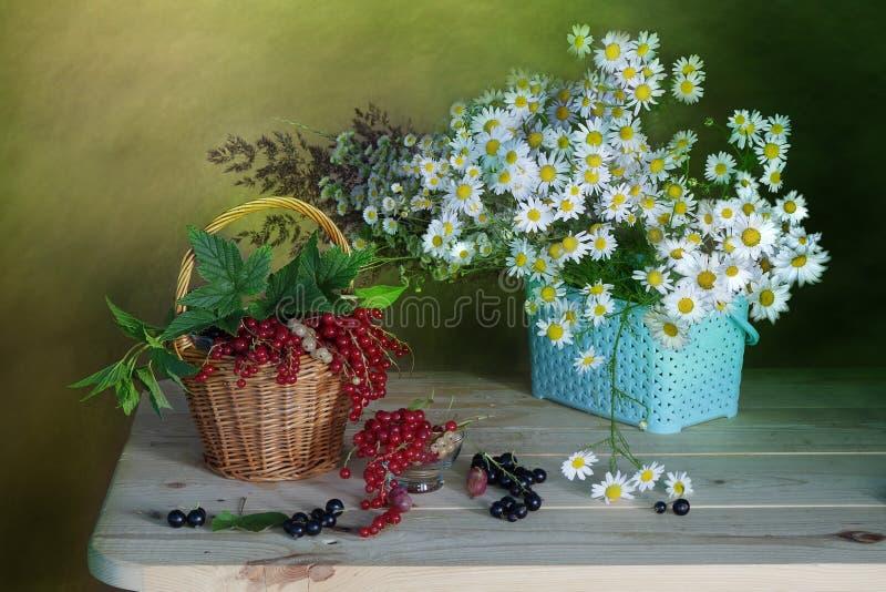 Wildflowers en rijpe, rode bessen in een mand stock afbeeldingen