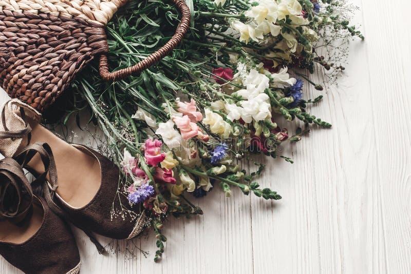 Wildflowers hermosos en zapatos de mimbre del bolso y de la mujer en wh rústico fotografía de archivo libre de regalías