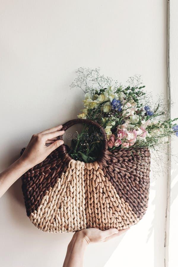 Wildflowers van de handholding in rieten zak bij rustiek venster Colorfu stock afbeelding