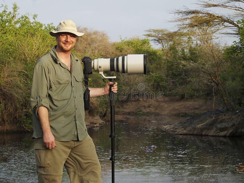 Wildlife photographer with long lens on camera in Africa. Photographer with large lens on African safari stock photography