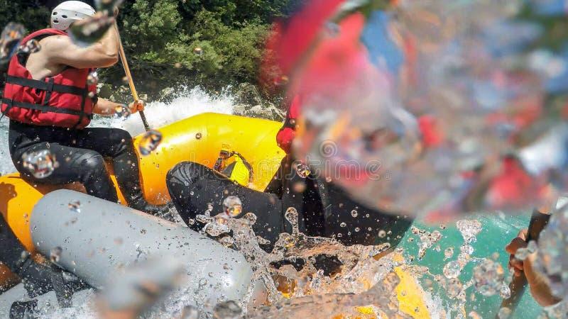 Wildwasserkanufahren-Boot gespritzt durch enorme Welle stockbild