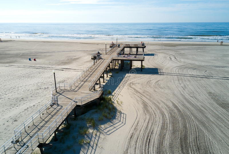 WILDWOOD, NEW JERSEY, USA - June 25, 2017: Crest beach and wooden dock from above with the ocean view and tourists relaxing. On the pier royalty free stock photo