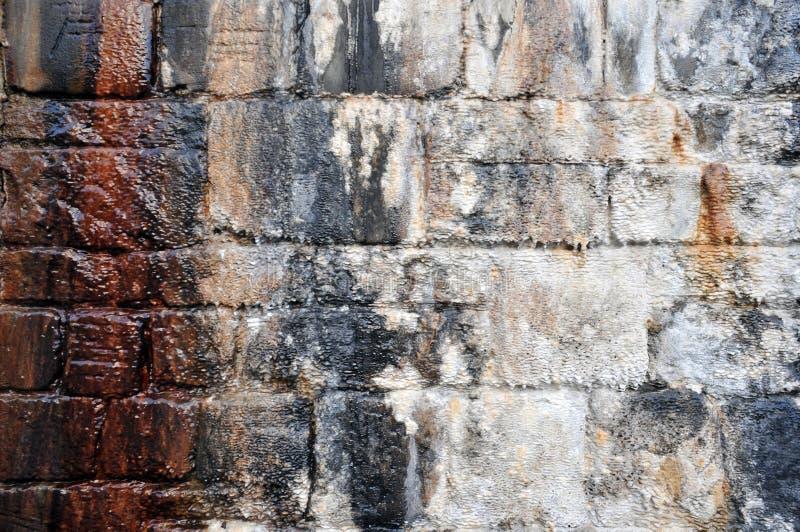 Wilgotna zewnętrzna kamienna ściana z wodnymi ocenami i białym kopalnym narzutem obraz stock