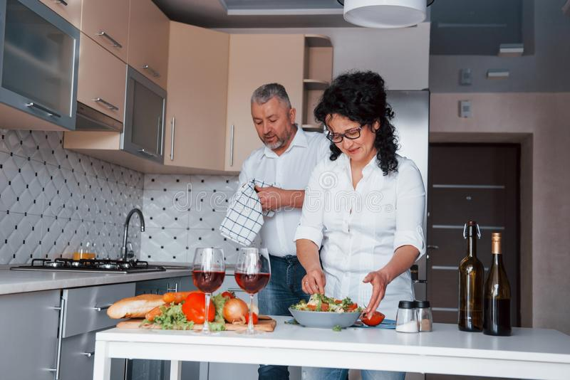 It will be nice dinner. Man and his wife in white shirt preparing food on the kitchen using vegetables stock image