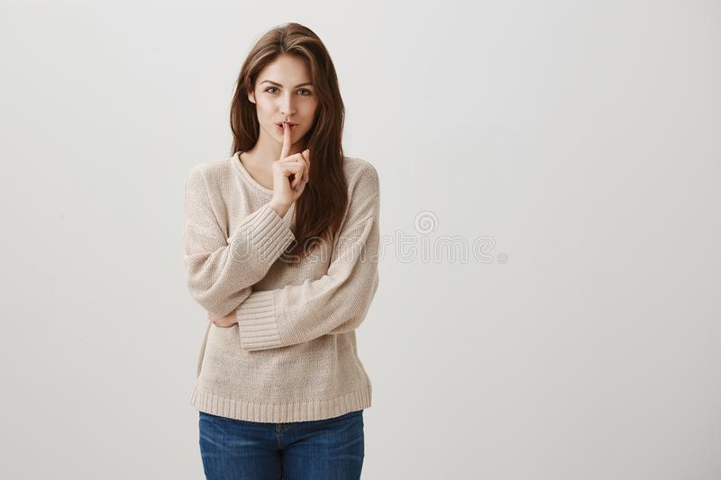 It will be our little secret. Studio shot of charming caucasian girl with long brunette hair smiling with interest while stock images