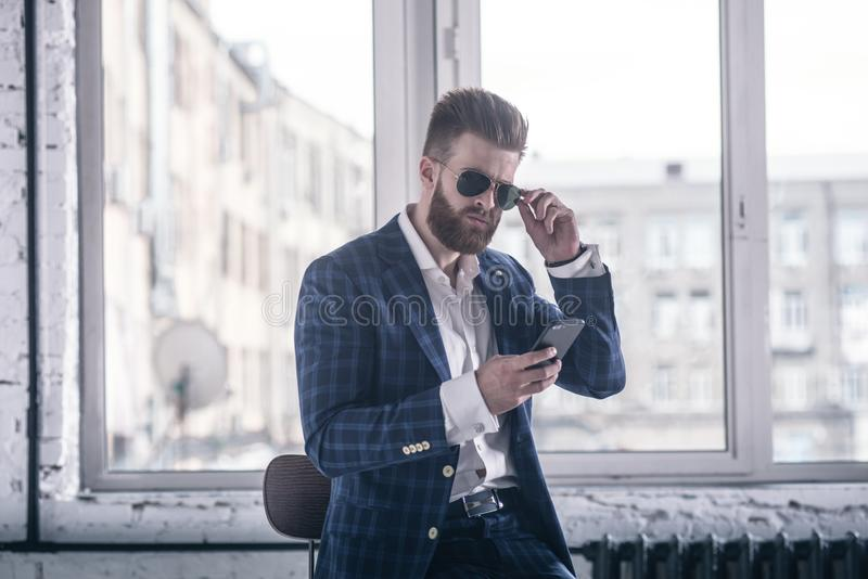 He will melt your heart. Handsome young bearded man in full suit and eyewear looking to his cell phone while sitting on the stool stock photos