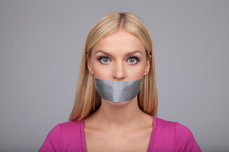 She will not gossiping anymore. Portrait of beautiful young women with her mouth covered with an adhesive tape standing isolated royalty free stock images
