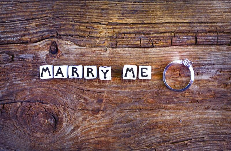 Will you marry me? An offer of marriage on rustic background. Wording `Marry me` written with little cubes and wedding ring near royalty free stock photos