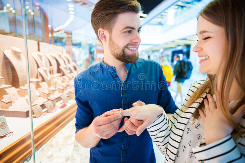 Will you marry me?. A photo of men proposing to his girlfriend at the mall, next to jeweller's shop stock photo