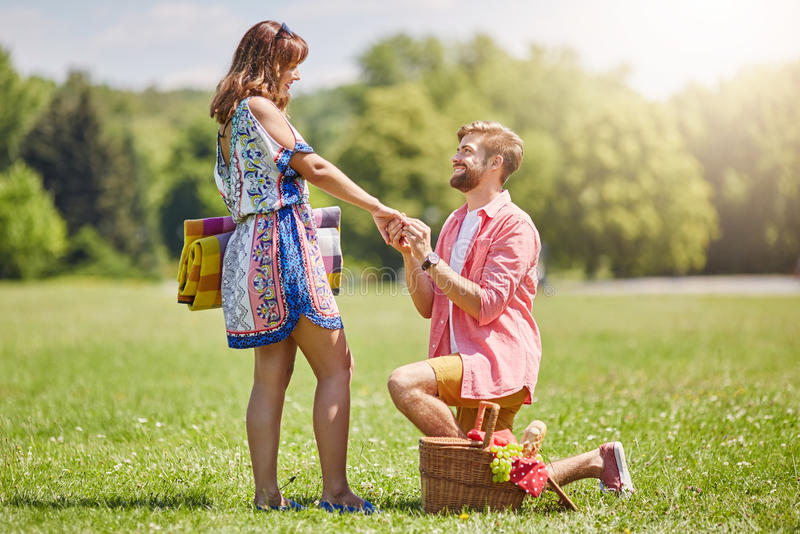 Will you marry me?. A photo of young men proposing to his girlfriend in the middle of the meadow royalty free stock photo