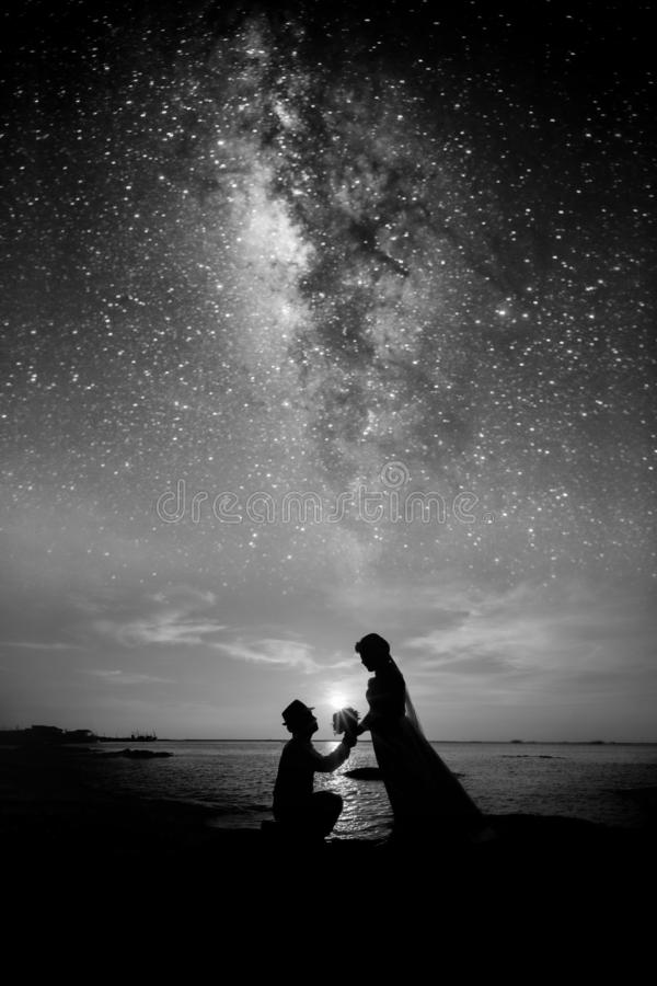 Will you marry me? Silhouette of young man staying on the knee and making proposal for his lovely girl on milky way Background.  stock photo
