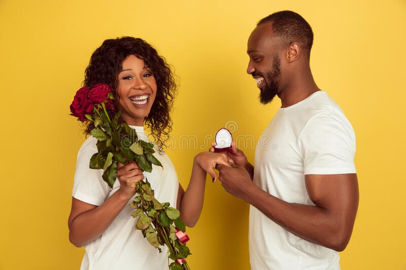 Valentine`s day celebration, happy african-american couple isolated on yellow background. Will you marry me. Valentine`s day celebration, happy african-american royalty free stock photography