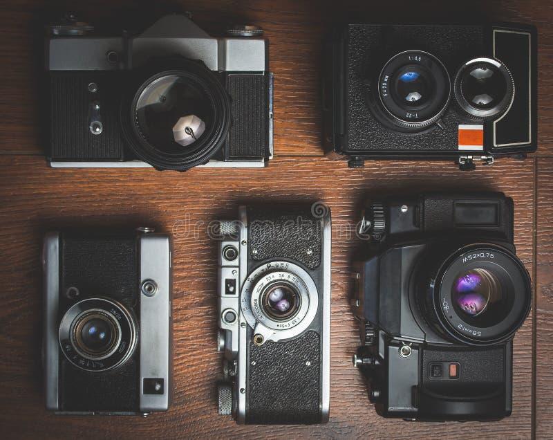 Willekeurige retro camera's op houten lijst stock afbeeldingen