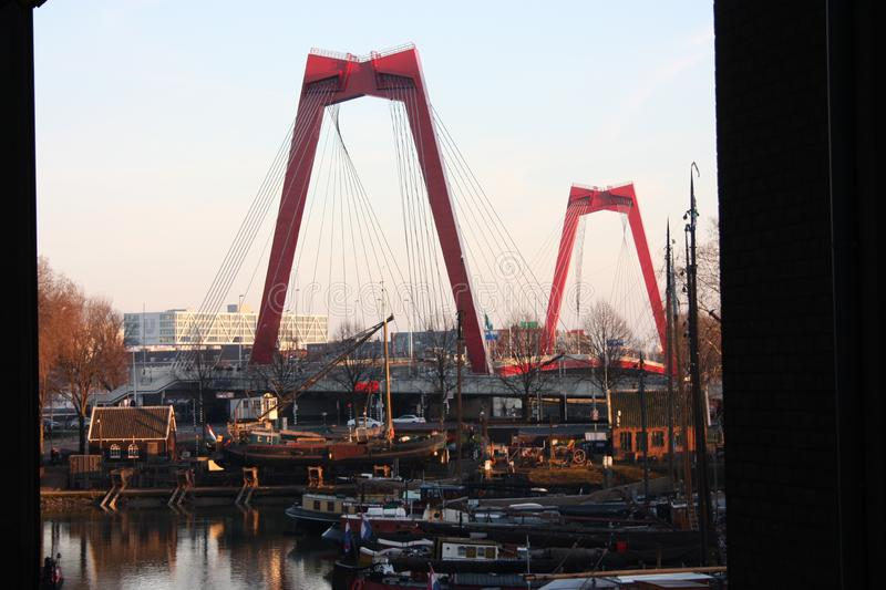 Willemsbrug, the red bridge in Rotterdam seen at sunset time over the harbor stock photography