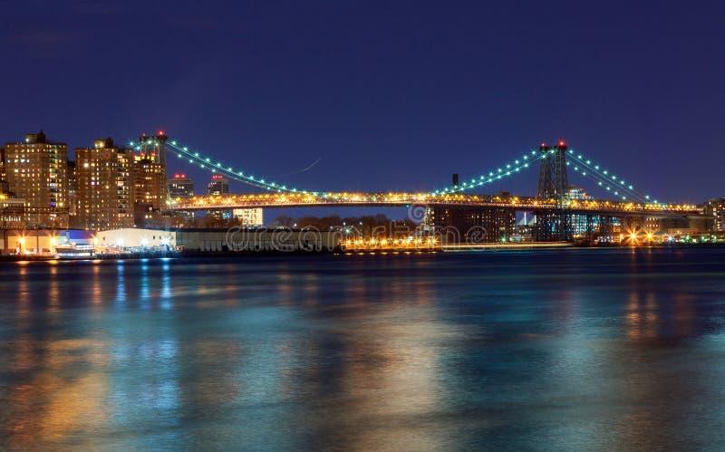 Williamsburgbrug die 's nachts, de Rivier van het Oosten tussen Brooklyn en Manhattan overspannen stock foto's