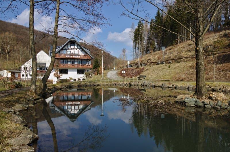Willingen、德国- 2018年3月27日, -反射在池塘的传统木构架和被粉刷的农舍 免版税图库摄影