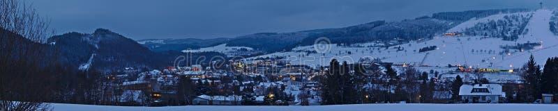 Willingen、德国- 2018年2月6日, -小滑雪胜地镇Willingen的全景射击有明亮地被点燃的房子和滑雪的s 库存照片