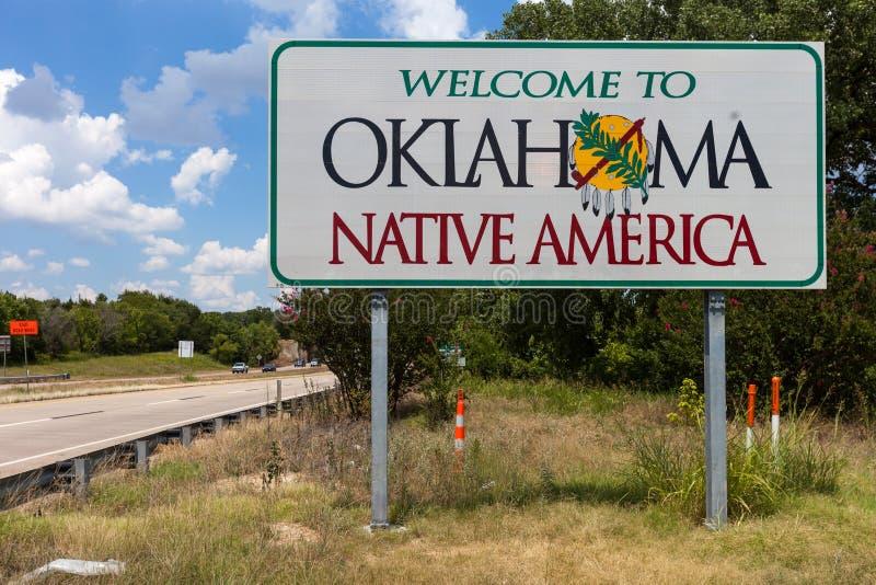Willkommen zu Oklahoma-Zeichen mit blauem Himmel und zu den Bäumen im Hintergrund stockbilder