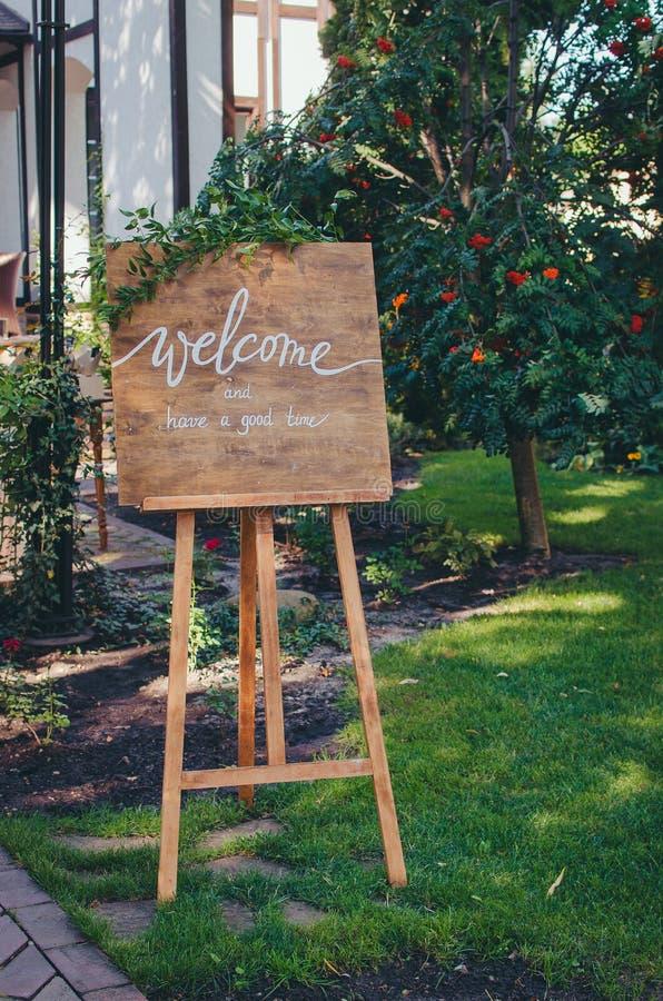 Willkommen zu unserer Feier Handgeschriebenes Kalligraphietext-Zeichenbrett auf Holzverkleidung im Garten mit dem Baumzweig lizenzfreies stockfoto