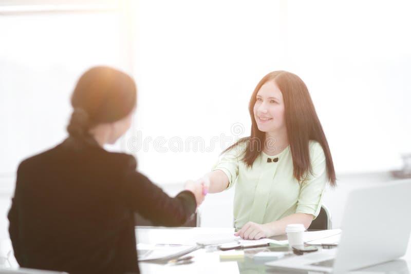 Willkommener Händedruck von zwei Geschäftsfrauen am Schreibtisch Foto mit Kopienraum stockfotografie