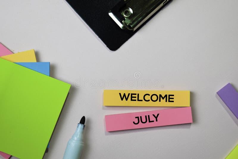 Willkommens-Juli-Text auf klebrigen Anmerkungen mit Schreibtischkonzept lizenzfreies stockbild