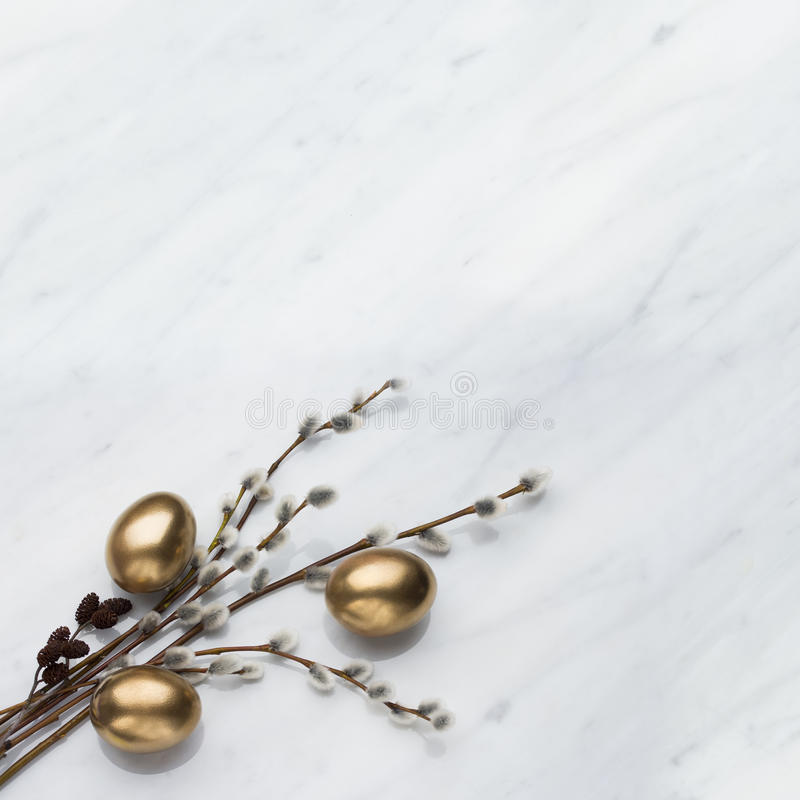 Willow and alder branches, golden eggs on Carrara marble counter. Willow and alder branches, golden eggs on Carrara marble kitchen worktop, easter concept royalty free stock images