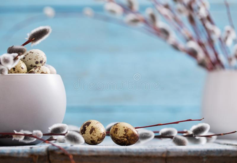 Willow branches and quail eggs on wooden background. Willow branches and quail eggs on a wooden background stock photo