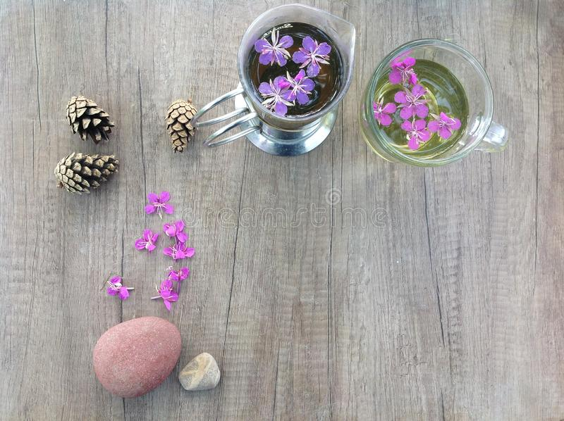 Willow herb Ivan tea in cup and topcup at the wood table workplace stock photo