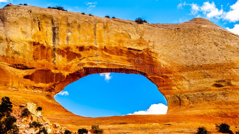 Wilson Arch under blue sky, a sandstone arch along US Highway 191, south of the town of Moab stock photography