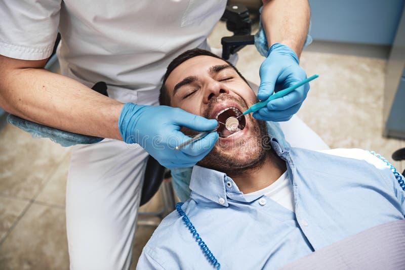 Wilt u een beter-kijkt glimlach? De tandarts in latex gloves het onderzoeken van mannelijke patiënt, liggend als tandvoorzitter m royalty-vrije stock afbeeldingen