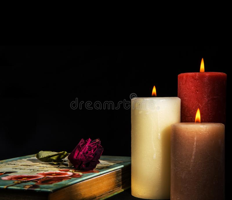 Wilted Faded red rose on book diary with three burning candles. Romantic Concept royalty free stock photography