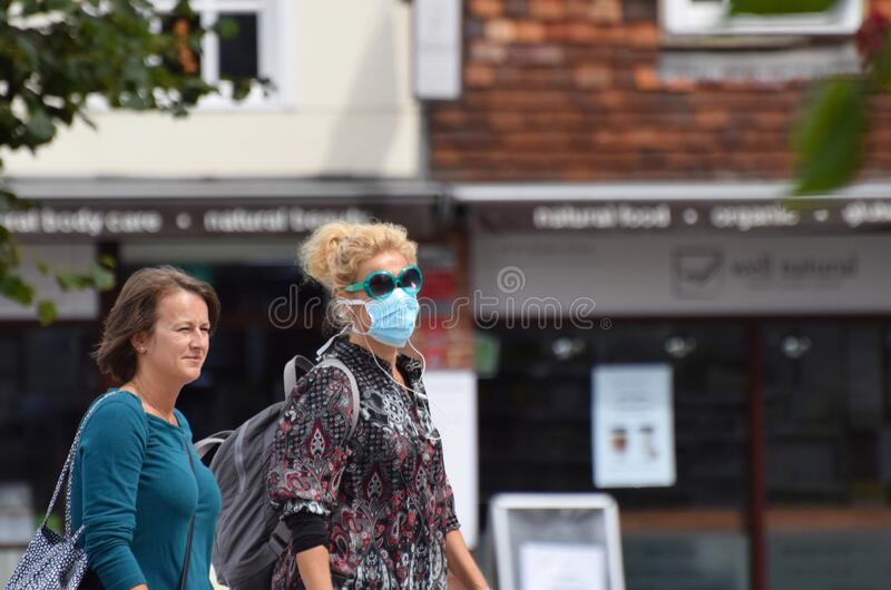 A woman wearing a face mask and matching sunglasses in public on the weekend that wearing face coverings became law in England royalty free stock photography